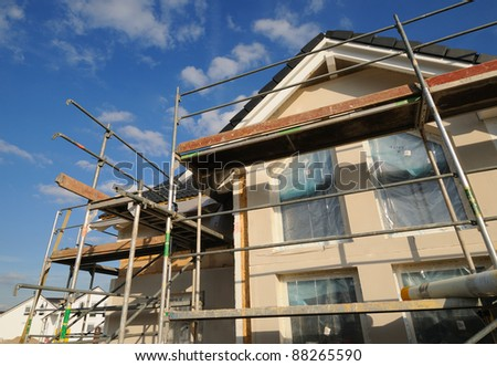 Construction site Construction site with a part of a dwelling house under a blue sky - stock photo