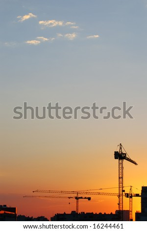 Construction site - cranes at dawn (vertical version) - stock photo