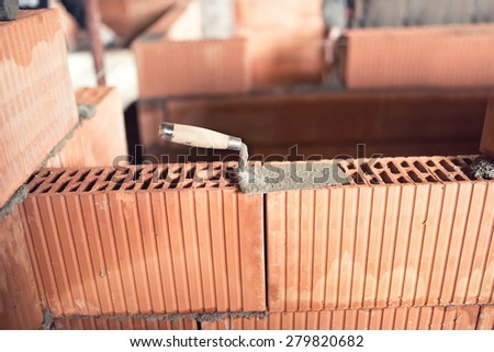 Construction site details and tools, trowel, putty knife on top of brick layer on interior walls - stock photo