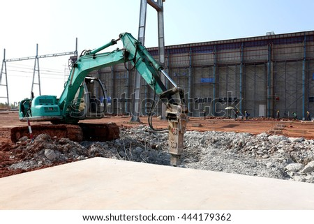 Construction site, excavator breaking and drilling the concrete