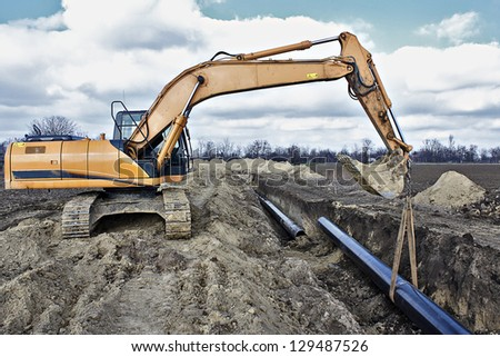 Construction site, excavator wearing metal pipe - stock photo