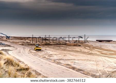 Construction Site excavators and bulldozer working on Katwijk beach  - stock photo