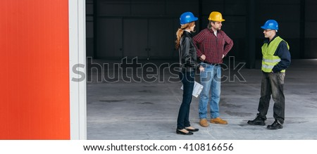 Construction Site Inspector talking with constructions workers - stock photo