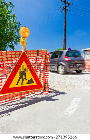 Construction site is protected by several traffic signs and orange fence with flashing beacon lights for safety. - stock photo