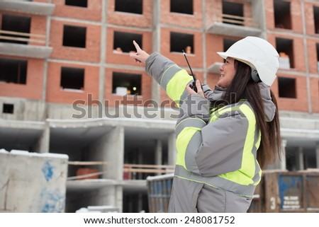 Construction site manager at construction site is inspecting ongoing production and commanding work by use of a radio. - stock photo
