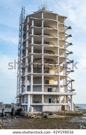 Construction site of building tower architecture on sea. - stock photo