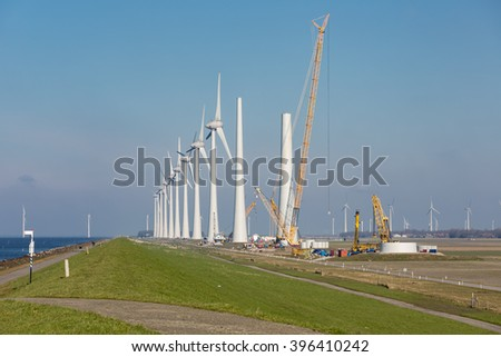 Construction site of new Dutch wind farm in agricultural landscape - stock photo