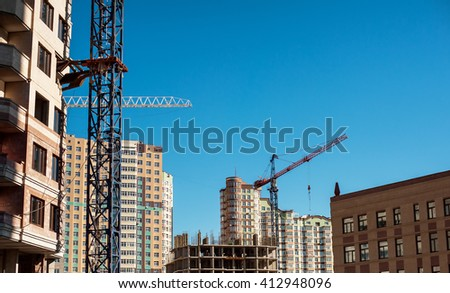 construction site of new skyscrapers and cranes against blue sky - stock photo