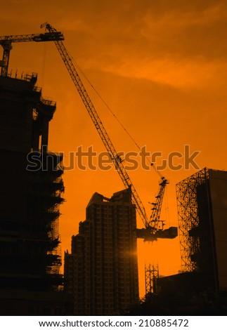Construction site - silhouette built crane structure industry - stock photo