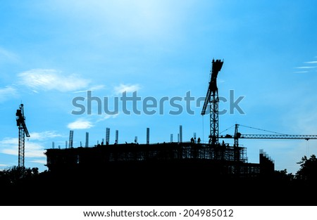 construction site silhouetted on daytime blue sky - stock photo
