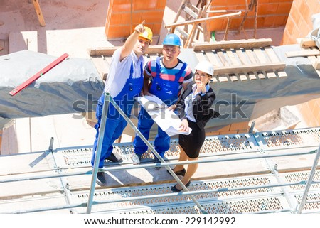 Construction site Team or architect and builder or worker with helmets discuss on a scaffold construction plan or blueprint or checklist  - stock photo