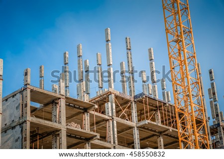 Construction site with a yellow crane and unfinished cbuilding with a blue sky/Construction of houses in new areas / disadvantages of the construction of residential buildings in Russia - stock photo