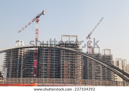 Construction site with building cranes and blue sky - stock photo