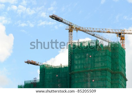 Construction site with crane and building against blue sky - stock photo