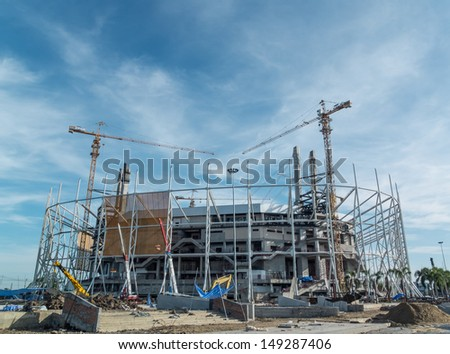 Construction site with crane and building on blue sky - stock photo