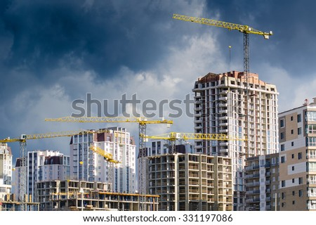 Construction site with cranes and unfinished buildings under the stormy sky. - stock photo