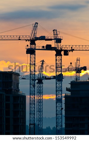 Construction site with cranes at sunset, sunrise, dawn time with the cranes as a silhouette. Vancouver, Canada. Vertical. - stock photo