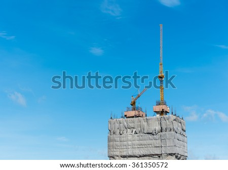 Construction site with cranes on blue sky - stock photo