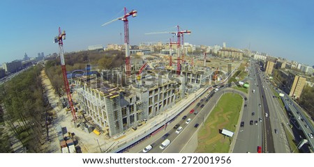 Construction site with lots of cranes next to the road, aerial view - stock photo