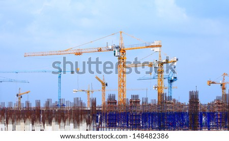 Construction site with multiple cranes on a blue background.
