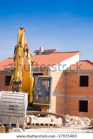 construction site with new house and heavy machinery - stock photo