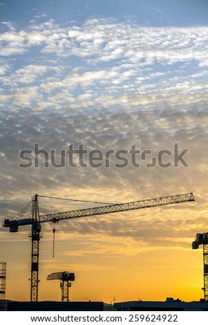 Construction site with tall cranes over sunrise cloudy sky - stock photo
