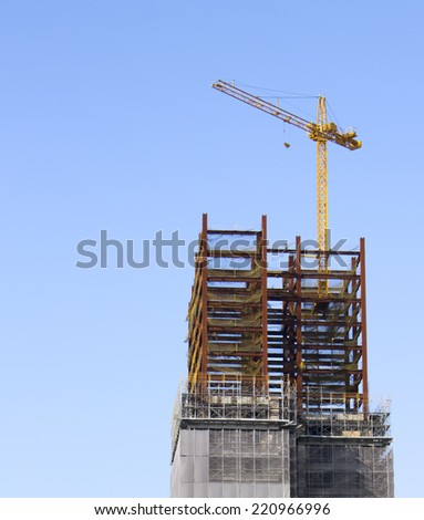 construction site with tower crane over blue sky - stock photo