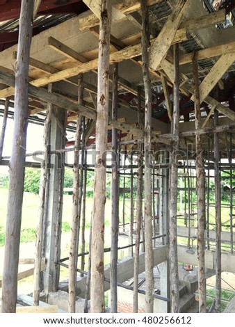Construction site : wooden columns supported cement plate on second floor