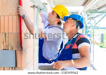 Construction site worker building a home or house doing bricklaying work on the walls of the shell  - stock photo