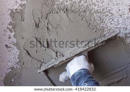 Construction site - Worker performs internal plaster raw - stock photo