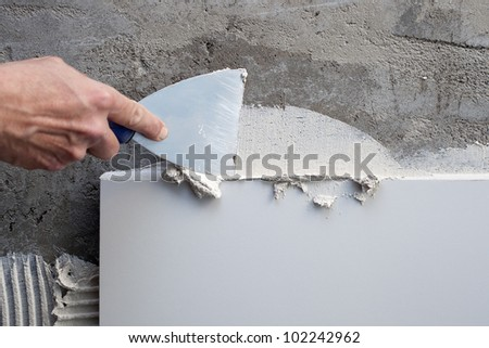 construction spatula trowel in tile work with white mortar