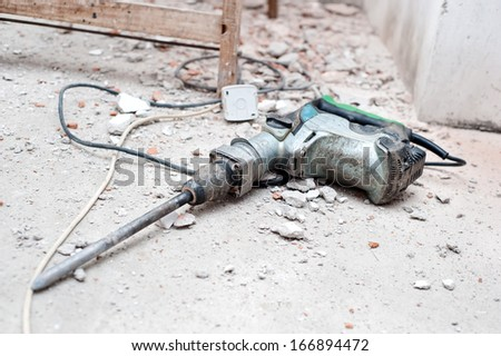 Construction tool, the jackhammer with demolition debris - stock photo