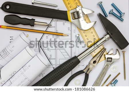 Construction tools and blueprints for a new house project - stock photo
