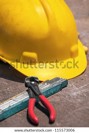 Construction tools - protective helmet, folded ruler, nippers for binding wires -  on construction workshop table - stock photo