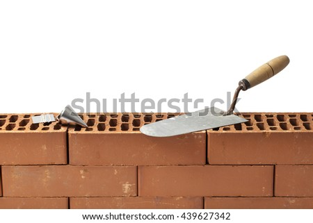 Construction tools trowel and plumb bob left on a new brickwork isolated on white. - stock photo
