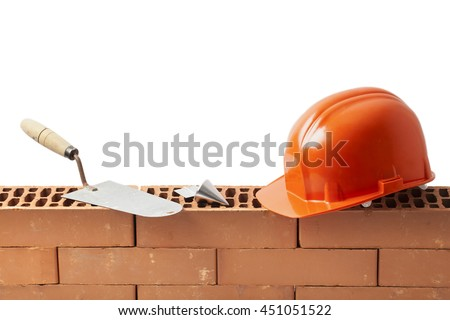 Construction tools trowel hard hat and plumb bob left on a new masonry isolated on white. - stock photo
