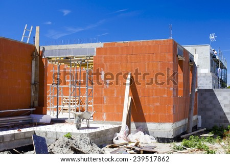 Construction work. Building of red brick cottage on blue sky background - stock photo