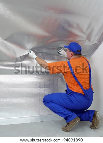 Construction worker affixing vapor insulation foil under thermally insulated attic surface - stock photo