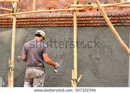 Construction worker and Plasterer being Building plaster on Temple wall