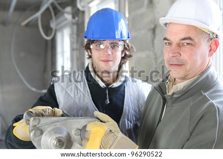 Construction worker and young helper - stock photo