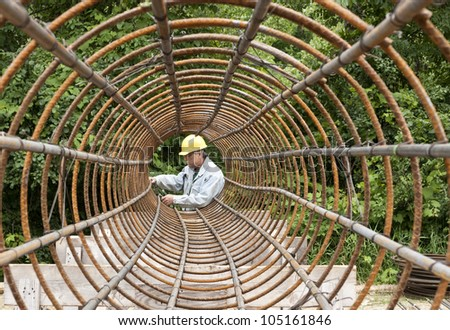 construction worker assembling rebar into a circular shape