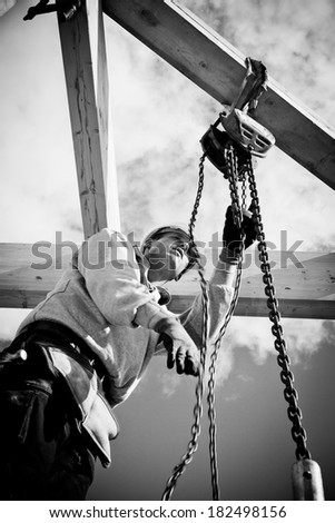 construction worker at work with winch on roof construction.Monochrome - stock photo