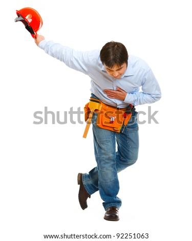 Construction worker bowing with helmet in hand - stock photo
