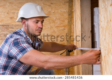 Construction Worker Builder Wearing White Hard Hat Measuring Width of Door Frame with Measuring Tape in Unfinished Home - stock photo