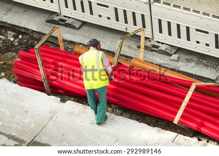 construction worker carrying a pvc pipe in city street - stock photo