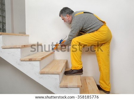 Construction worker caulking wooden stairs with silicone glue using cartridge, home renovation - stock photo