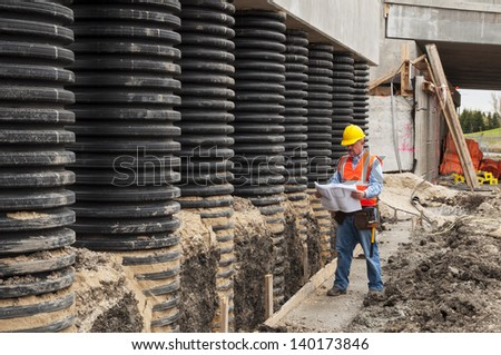 Construction worker checking blueprint at bridge construction site - stock photo