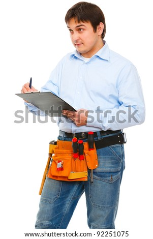 Construction worker checking something and writing in clipboard