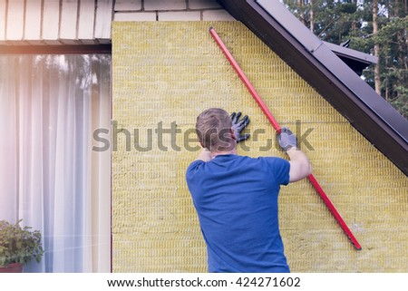 construction worker checks the level of insulated house wall - stock photo