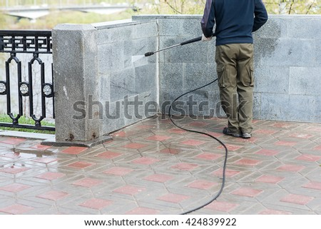 Construction worker cleaning street with water hose - stock photo